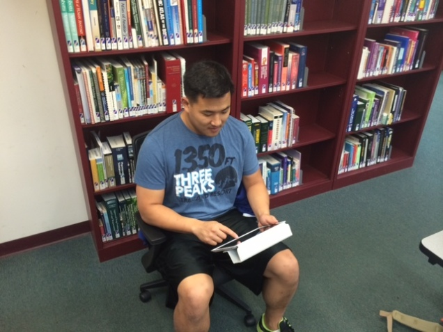 PT student using I-pad in the library.