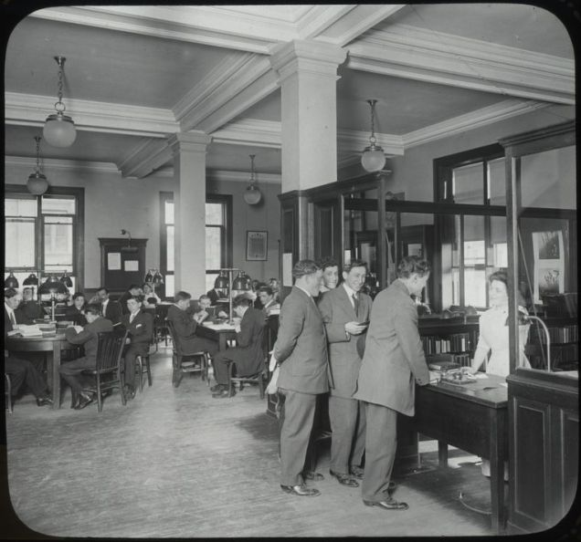 young men at reference desk, early 20th century