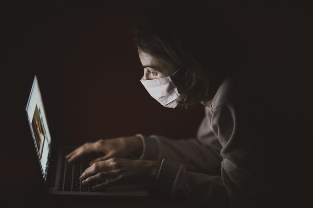 a woman wearing a mask looking at an image on a laptop