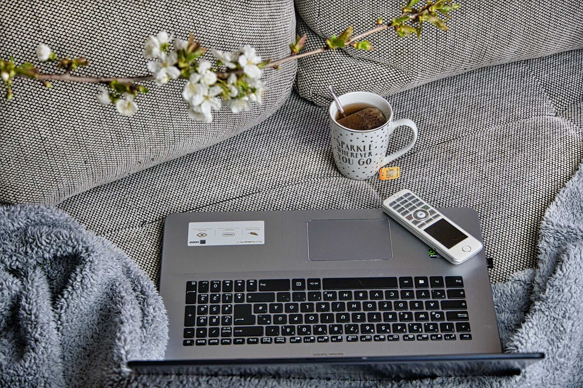 a laptop and phone and mug on a couch