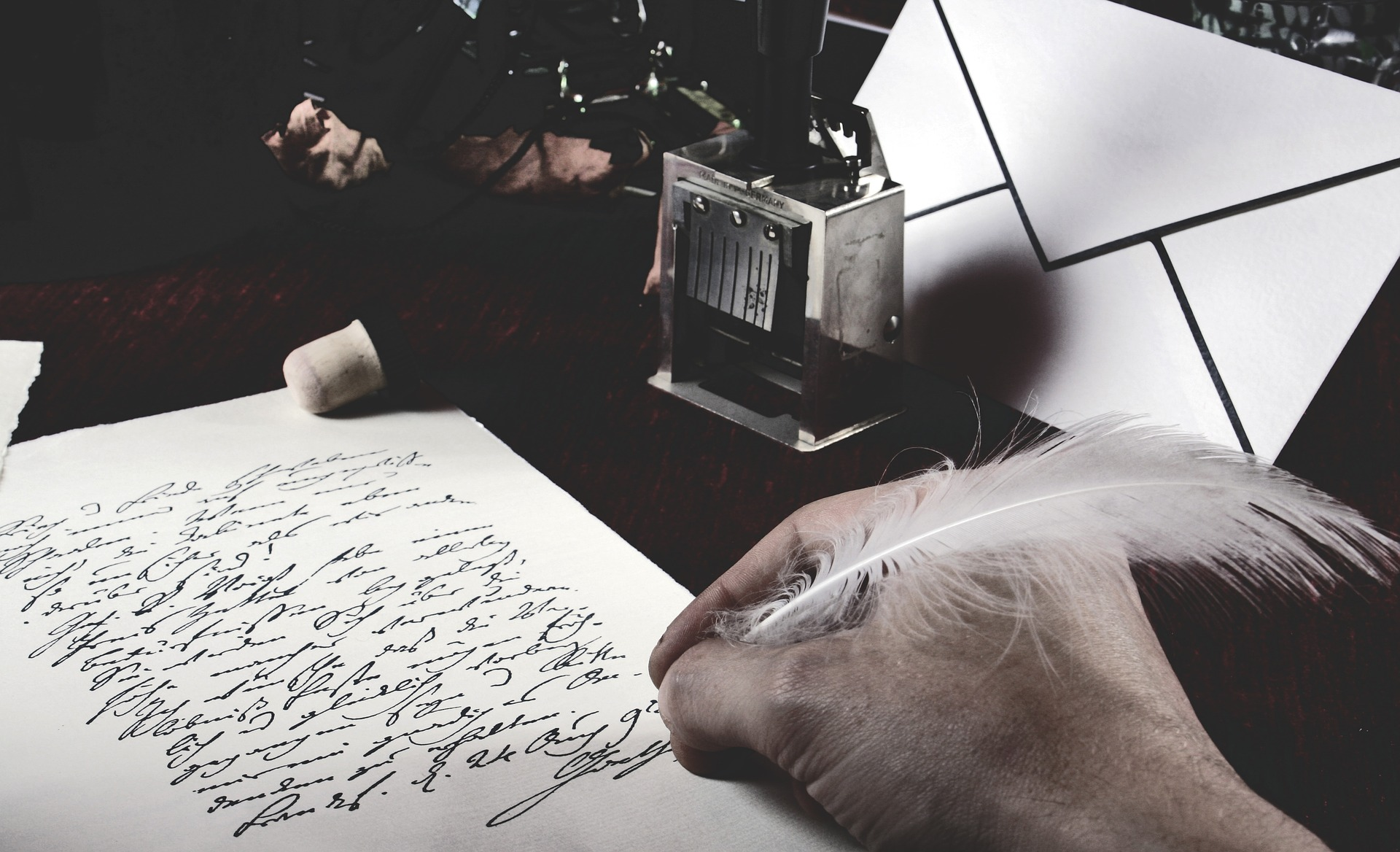 a hand writing with a quill