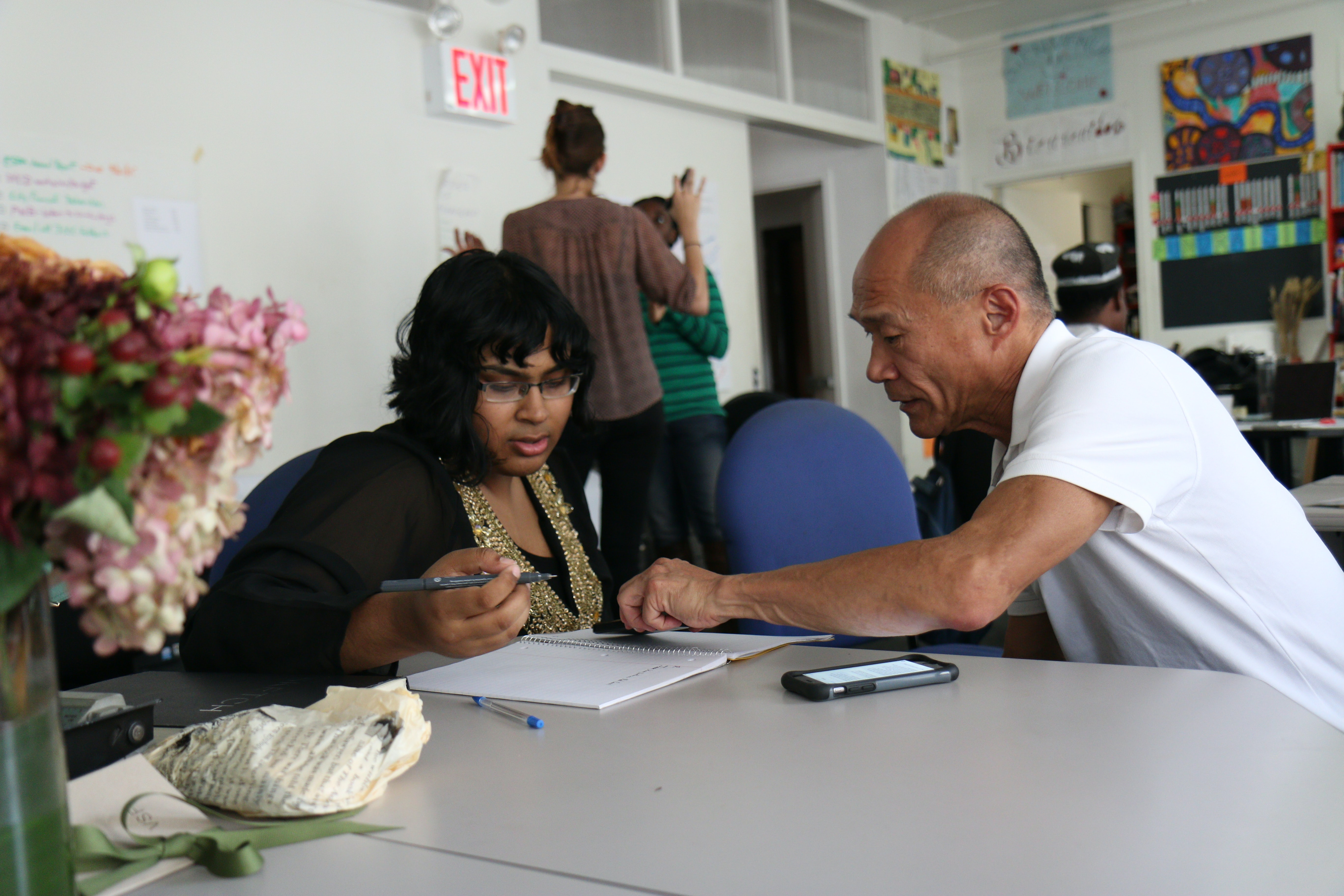 a man teaching a woman sitting at a table