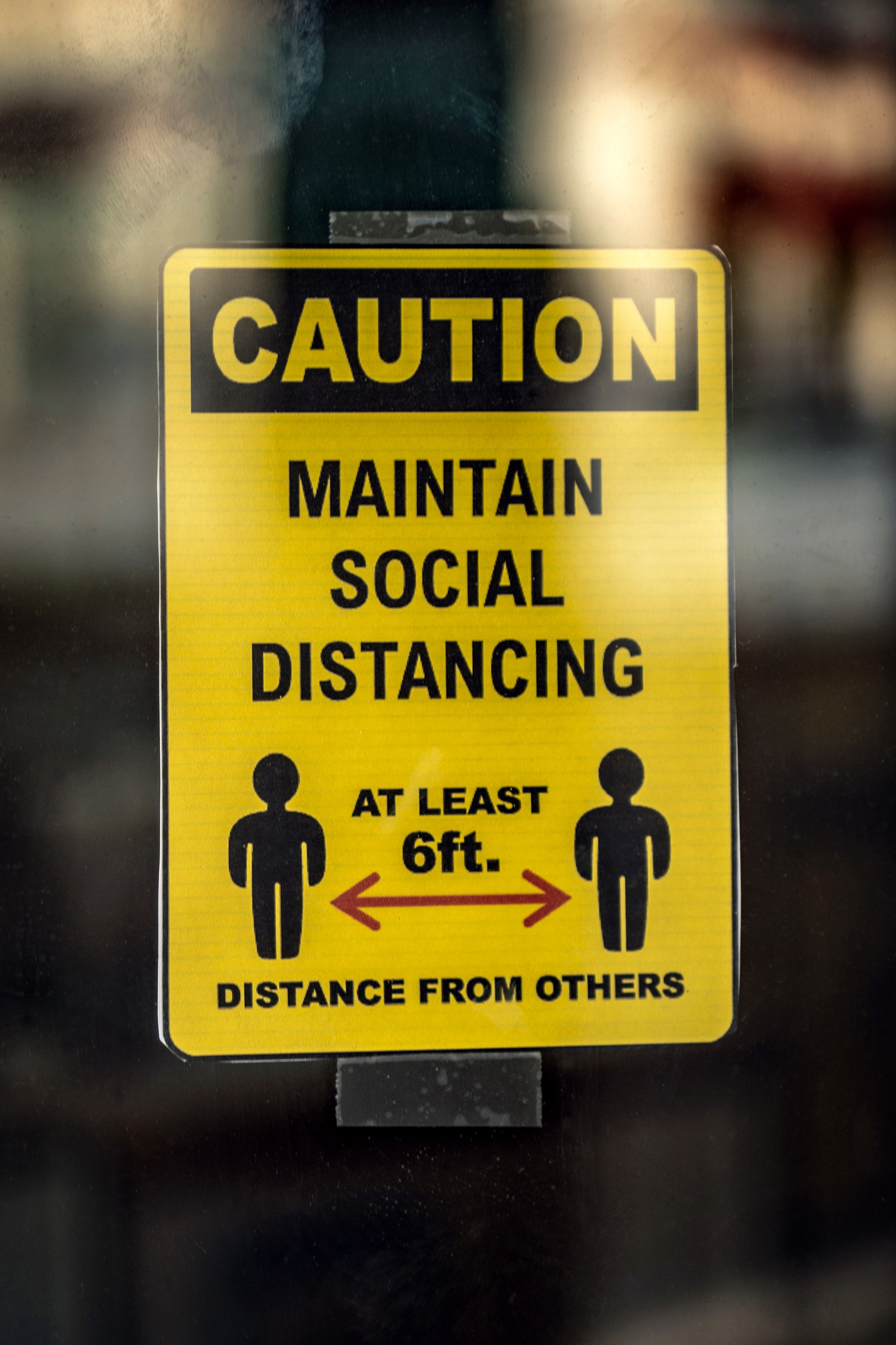 "a sign that reads ""Caution: Maintain social distancing, at least 6 ft distance from others"