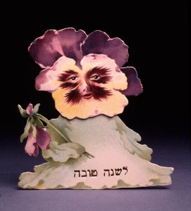 Rosh Hashanah / New Year greeting card:A Pansy with a face bears the Hebrew inscription for a happy New Year.